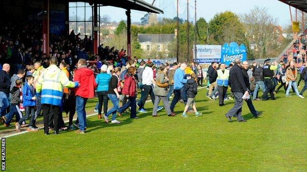 Fans in the Stagecoach Stand are evacuated onto the pitch