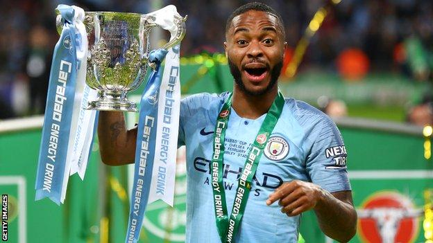 Manchester City forward Raheem Sterling smiles as he holds up the Carabao Cup trophy