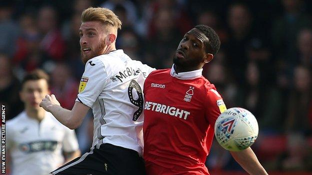 Oli McBurnie of Swansea City is challenged by Molla Wague of Nottingham Forest