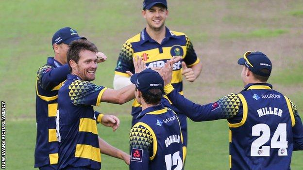 Glamorgan bowler Michael Hogan (L) celebrates a wicket with David Miller