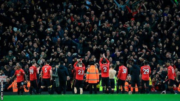 Manchester United players applaud the crowd after their game with Manchester City in December