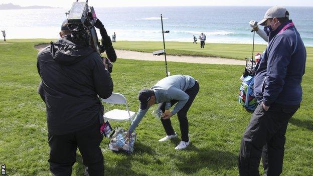 Jordan Spieth retrieving his ball from a volunteer's bag at the Pebble Beach Pro-Am