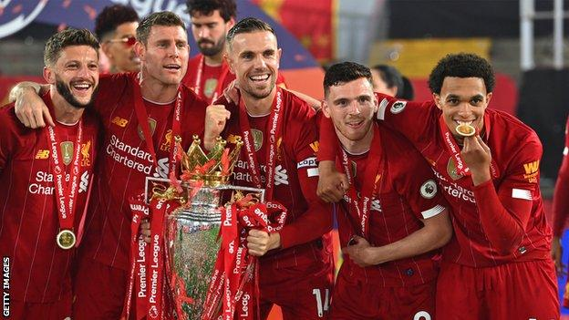 Liverpool players (from left to right) Adam Lallana, James Milner, Jordan Henderson, Andrew Robertson and Trent Alexander-Arnold celebrate with the Premier League trophy