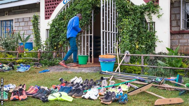 General scene of camp entrance, shoes littered on grass next to mops and brooms