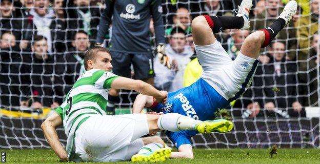 Kenny Miller receives a heavy challenge from Celtic defender Jozo Simunovic