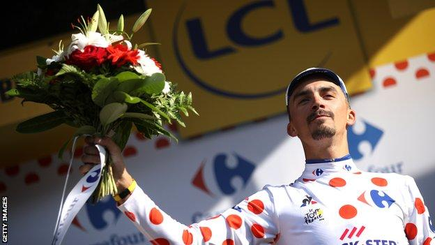 Julian Alaphilippe raises a bouquet of flowers to celebrate winning stage 10
