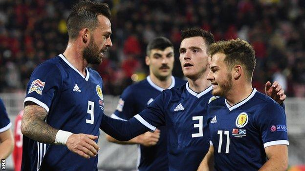 Steven Fletcher celebrates a Scotland goal with Andy Robertson and Ryan Fraser