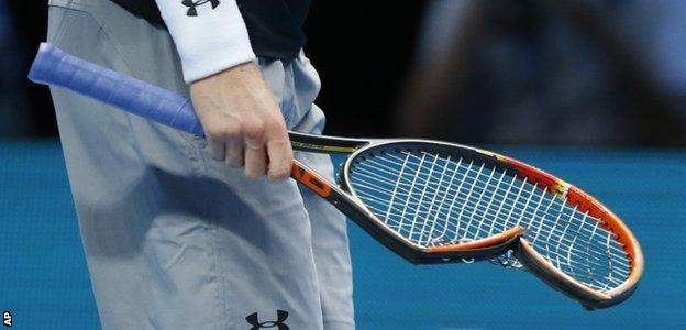 Andy Murray of Britain carries his smashed racquet back to his seat as he plays against Stan Wawrinka of Switzerland in their singles tennis match