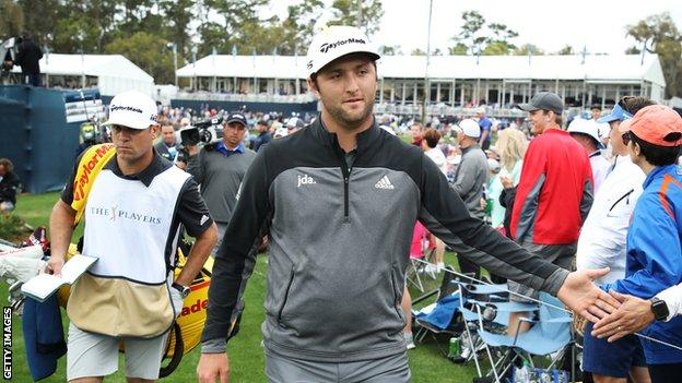 Jon Rahm high-fives a spectator during the third round of the Players Championship