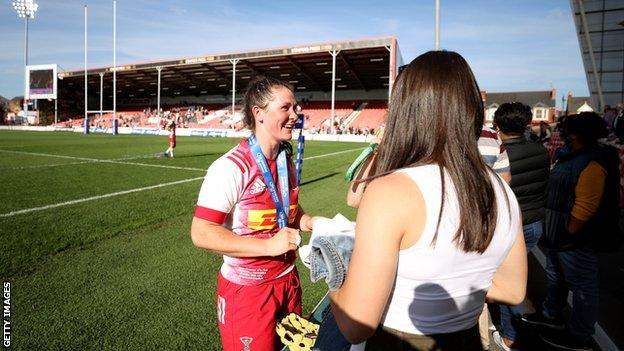 Emily Robinson wears a winners' medal and talks to fans