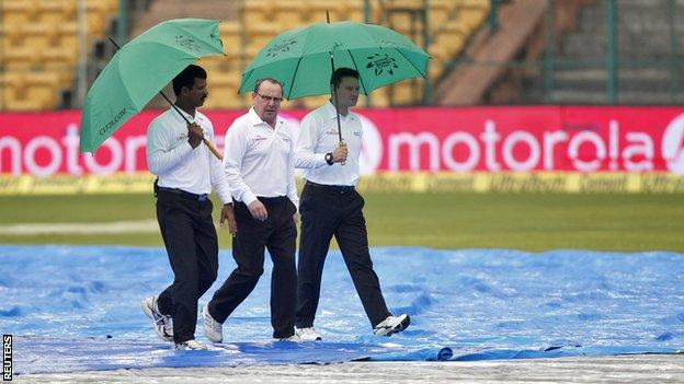 The umpires shelter from the rain in Bangalore