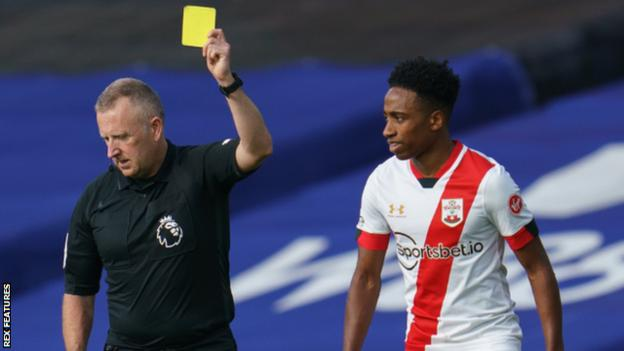 Referee Jonathan Moss shows Kyle Walker-Peters a yellow card