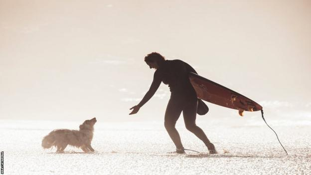 Maya plays with one of her dogs at Nazare