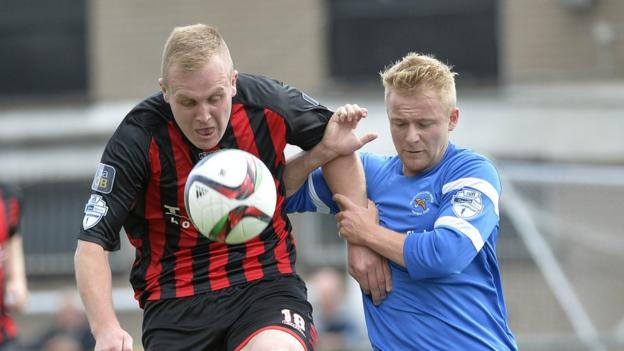 Jordan Owens battles for possession with John Currie during Crusaders's 5-0 thumping of Ballinamallard United at Seaview