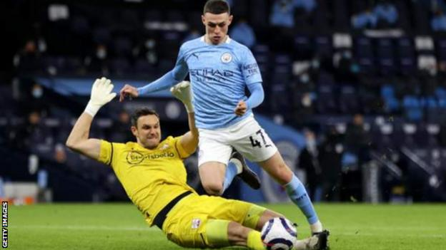 Southampton keeper Alex McCarthy challenges Manchester City's Phil Foden