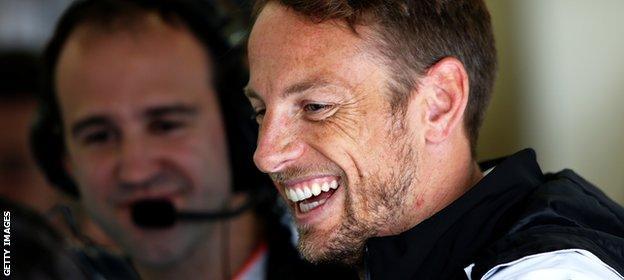 Jenson Button smiles in the McLaren garage