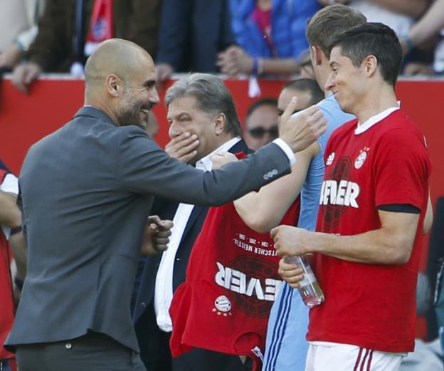 Bayern Munich boss Pep Guardiola celebrates with Robert Lewandowski after the final whistle