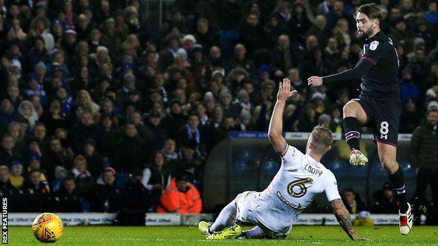 Henri Lansbury scores for Aston Villa as Leeds United's Liam Cooper tries to make the block