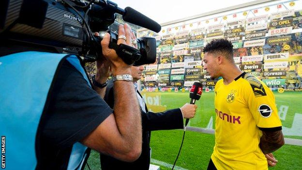 Jadon Sancho is interviewed on the pitch after a game