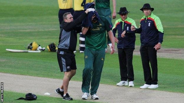 Nottinghamshire bowler Luke Fletcher is helped from the field after being struck by a ball during a Twenty20 mach against Birmingham