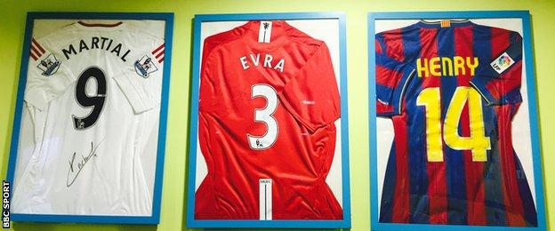 Shirts from Martial, Evra and Henry hanging on the wall at Les Ulis