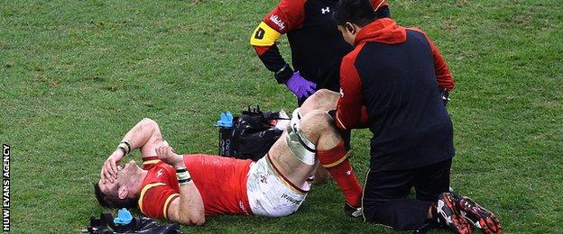 Dan Lydiate receiving treatment after injuring a knee playing for Wales against South Africa