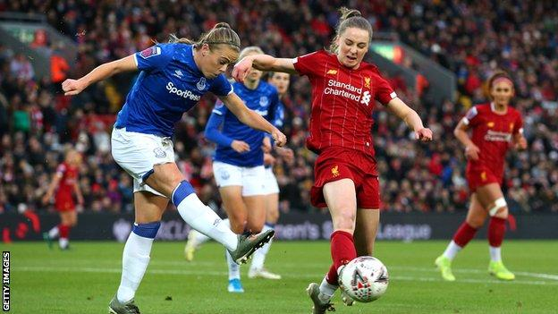 Everton's Simone Magill clears the ball from Liverpool's Niamh Charles in the WSL derby at Anfield in November 2019