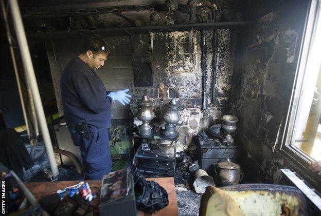 A policeman examines the scene after a fire at Beitar in February 2013. Police said arsonists torched the club offices over the signing of two Muslim footballers from Chechnya