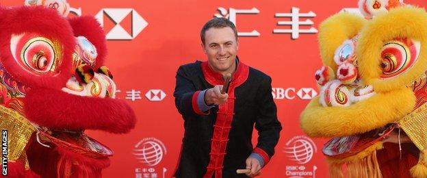 Jordan Spieth performs on stage with two Chinese dragons during a photocall for the Champions Tour in Shanghai