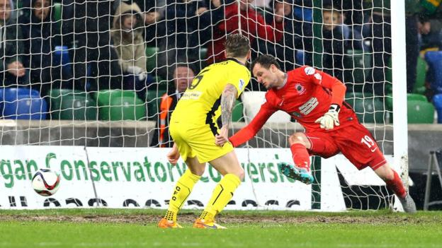 Linfield keeper Ross Glendinning can only watch on as Jay Donnelly's strike clinches a 2-1 victory for Cliftonville