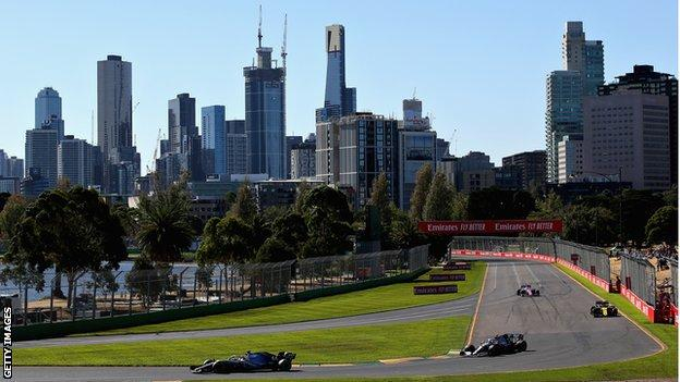 Cars go round the track in Melbourne in bright sunshine