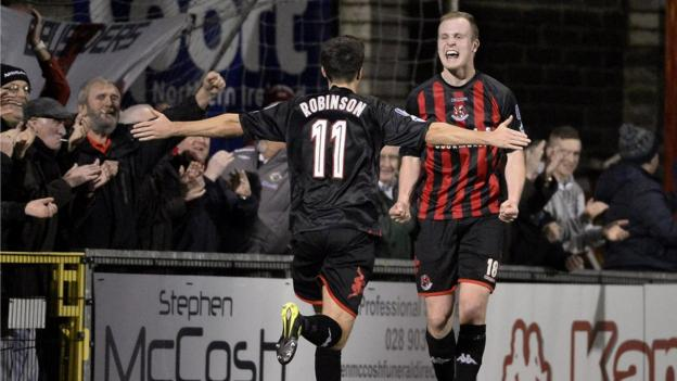 Josh Robinson prepares to congratulate Jordan Owens after the striker makes it 3-1 to Crusaders against Coleraine
