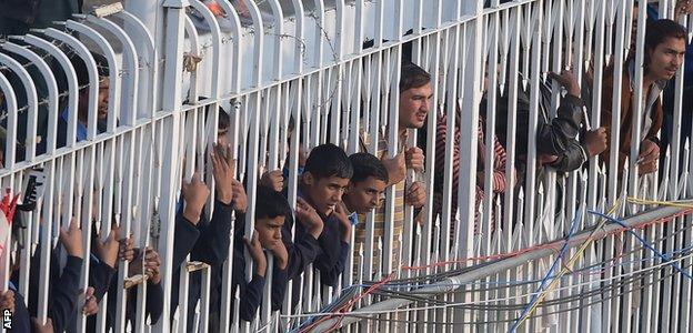Fans peer through a fence