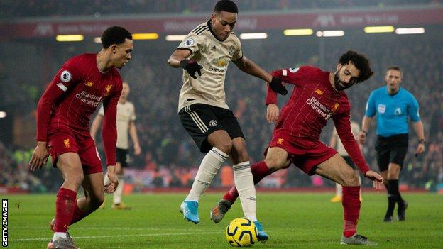 Manchester United's Anthony Martial holds off Liverpool's Mohamed Salah and Trent Alexander-Arnold