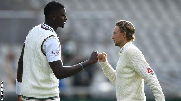Jason Holder (left) and Joe Root (right) fist pump after the second Test at Emirates Old Trafford