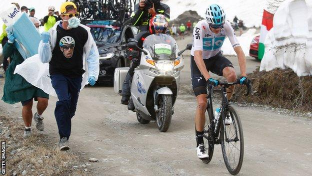 Spectators wearing surgical masks and carrying a giant inhaler run alongside Chris Froome during his Giro d'Italia win in May