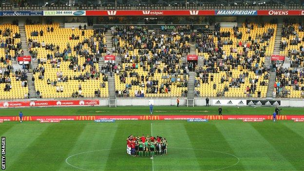 Players and officials form a huddle in support of victims of the Christchurch mosque shootings during the match between the Wellington Phoenix and the Western Sydney Wanderers at Westpac Stadium in Wellington