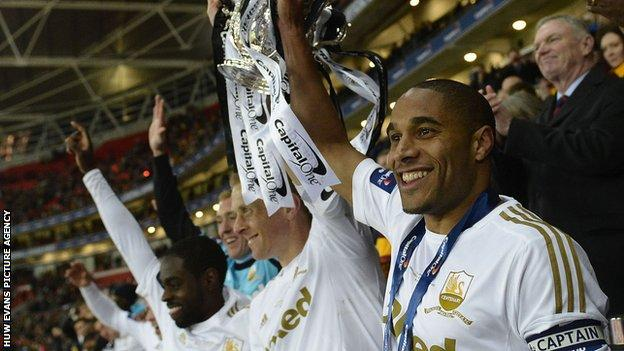 Ashley Williams (right) and Garry Monk (centre) lift the League Cup trophy