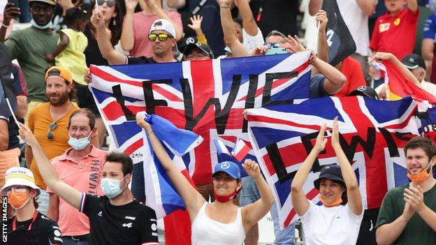 Fans at the French grand prix hold their Lewis Hamilton flags aloft