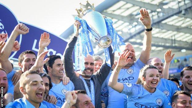 Pep Guardiola holds aloft the Premier League trophy