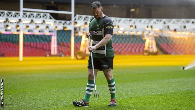 Rhys Cleverly works on the Principality Stadium pitch while wearing Caerphilly kit