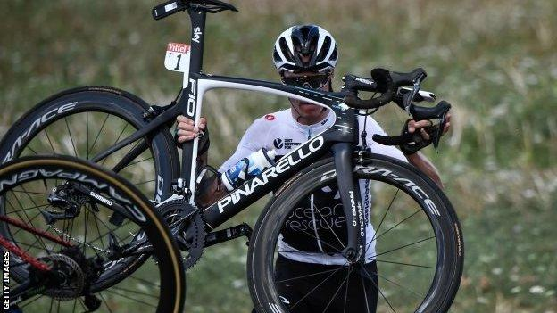 Chris Froome lifts his bike back on to the road after crashing on stage one