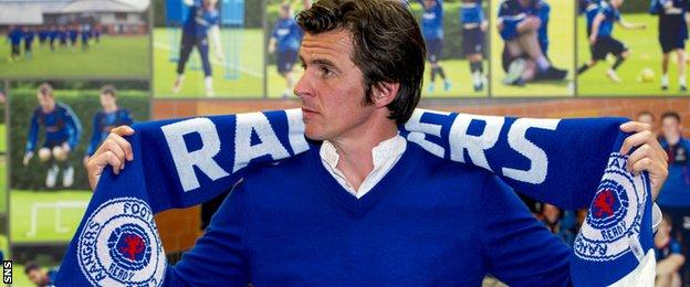 Joey Barton poses with a Rangers scarf after being presented to the media