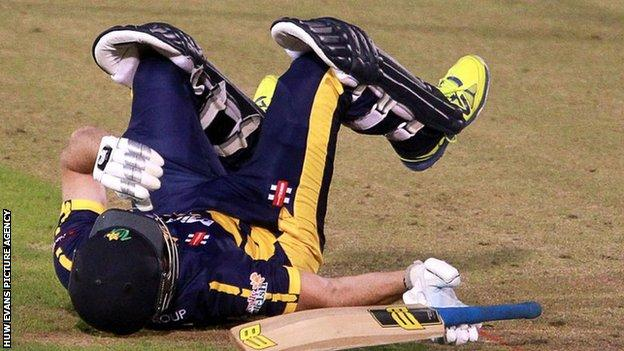 Graham Wagg falls to the ground after being struck on the head
