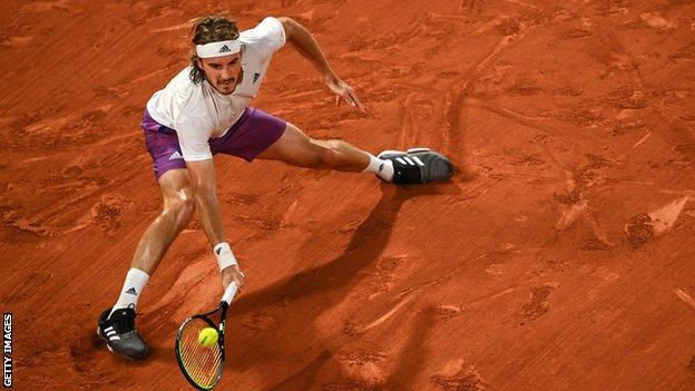 Stefanos Tsitsipas stretches for a return against Daniil Medvedev in their French Open quarter-final