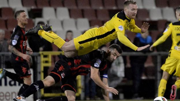 Chris Curran of Cliftonville takes a tumble after a challenge by Crusaders skipper Colin Coates during the 2-2 draw at Seaview