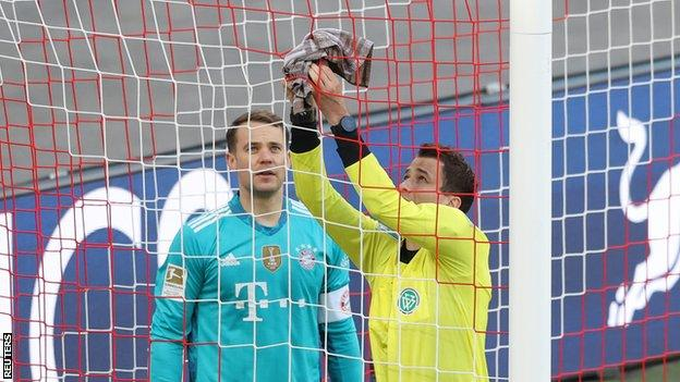 The assistant referee uses Manuel Neuer's towel to try and fix a hole in the net