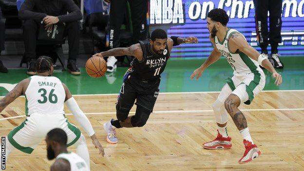 Brooklyn Nets guard Kyrie Irving dribbles the ball past two Boston Celtics players