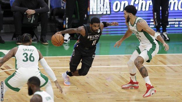 Brooklyn Nets'in gardiyanı Kyrie Irving topu iki Boston Celtics oyuncunun yanından geçiriyor