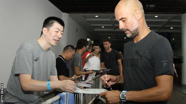 Pep Guardiola signs an autograph for a Chinese fan